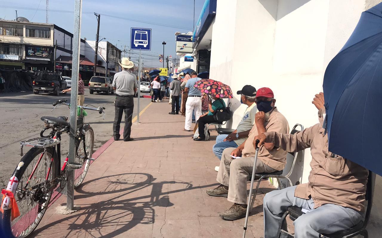 Bajo el sol hacen largas filas en BANAMEX para cobrar pensión adultos mayores de Monclova