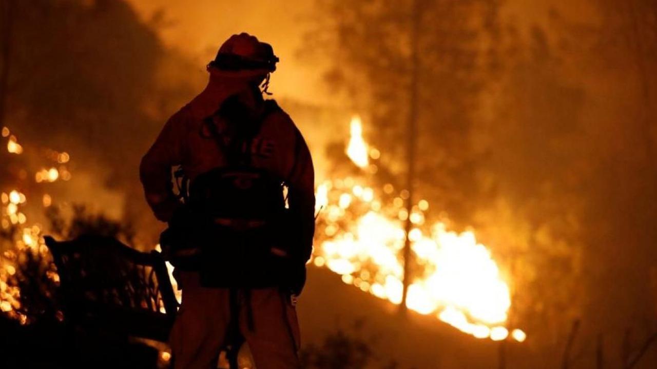 Bomberos se refugian en río para salvarse de un incendio forestal