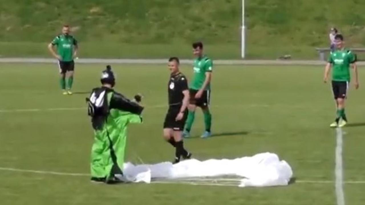 Paracaidista cae en cancha de fútbol en pleno partido